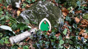 green elf door on rock